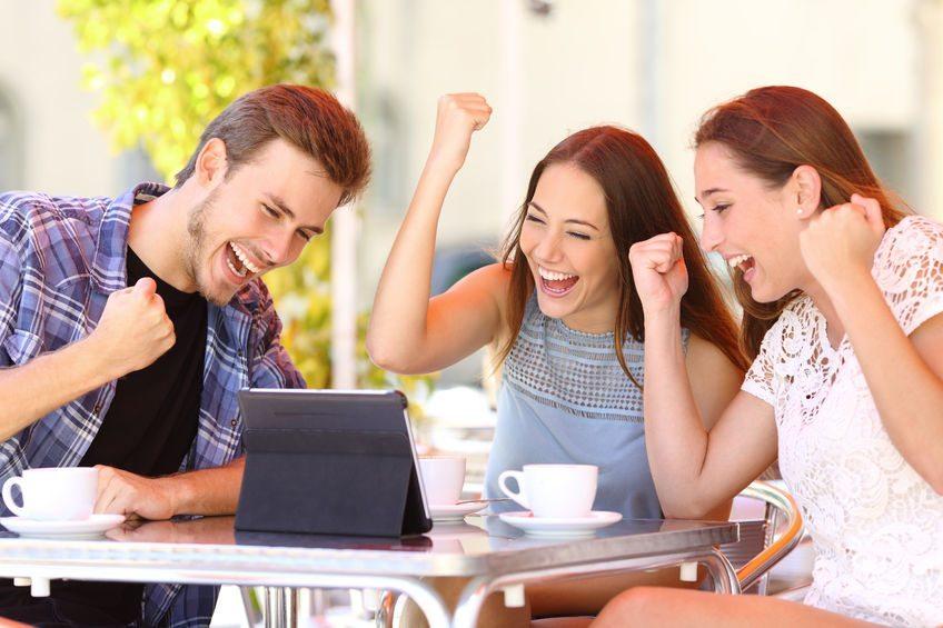 44683564 - euphoric winner friends using a tablet in a coffee shop terrace